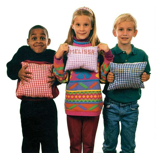 Children holding name sampler pillows made from My First Embroidery Book